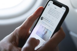 person reading tweet on iphone