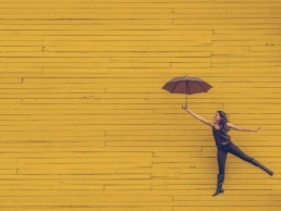woman jumping in front of yellow wall