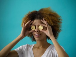 Woman holding gold coins to her eyes